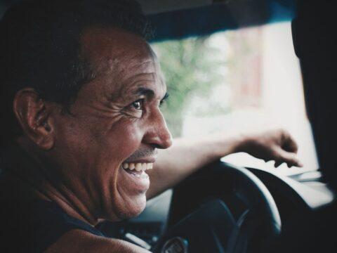 Esmer kavruk bir adam sürücü koltuğunda yanındaki arkadaşına bakarak gülüyor.