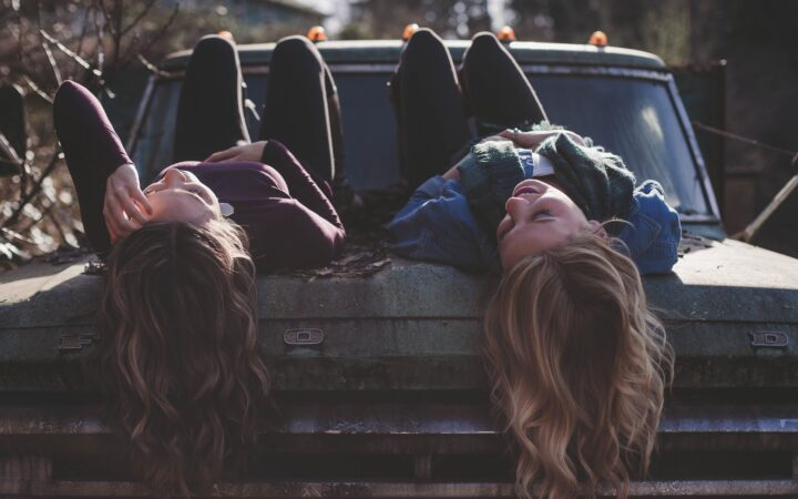 İki tane genç kız bir arabanın bagaj kapağına yatmış sohbet ediyorlar.