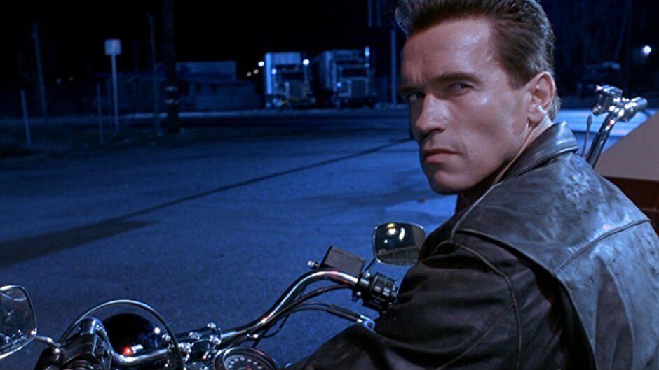 Arnold Schwarzenegger motosikletin üstünde bize bakıyor.
