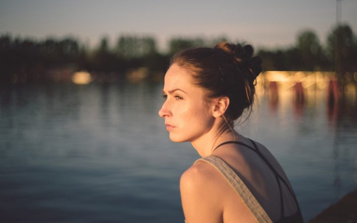 Asık suratlı kadın sahilde oturuyor.