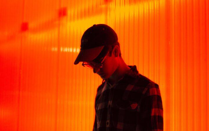 Boynu bükük yere bakan şapkalı, gözlüklü bir genç.