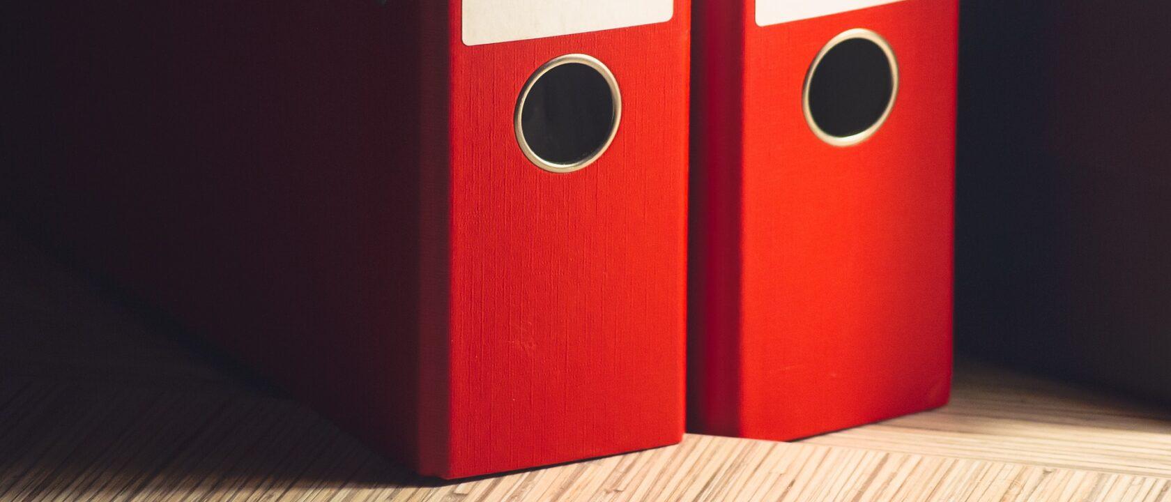 Bir masanın üzerinde iki adet kırmızı telli dosya duruyor.