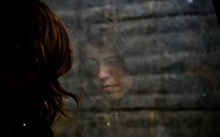 Düşünceli kadının kendi yansıması baktığı camda görülüyor.