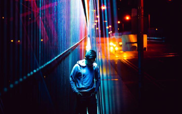 Gece vakti sokak lambalarıyla ışık oyunlarının arasında yürüyor.