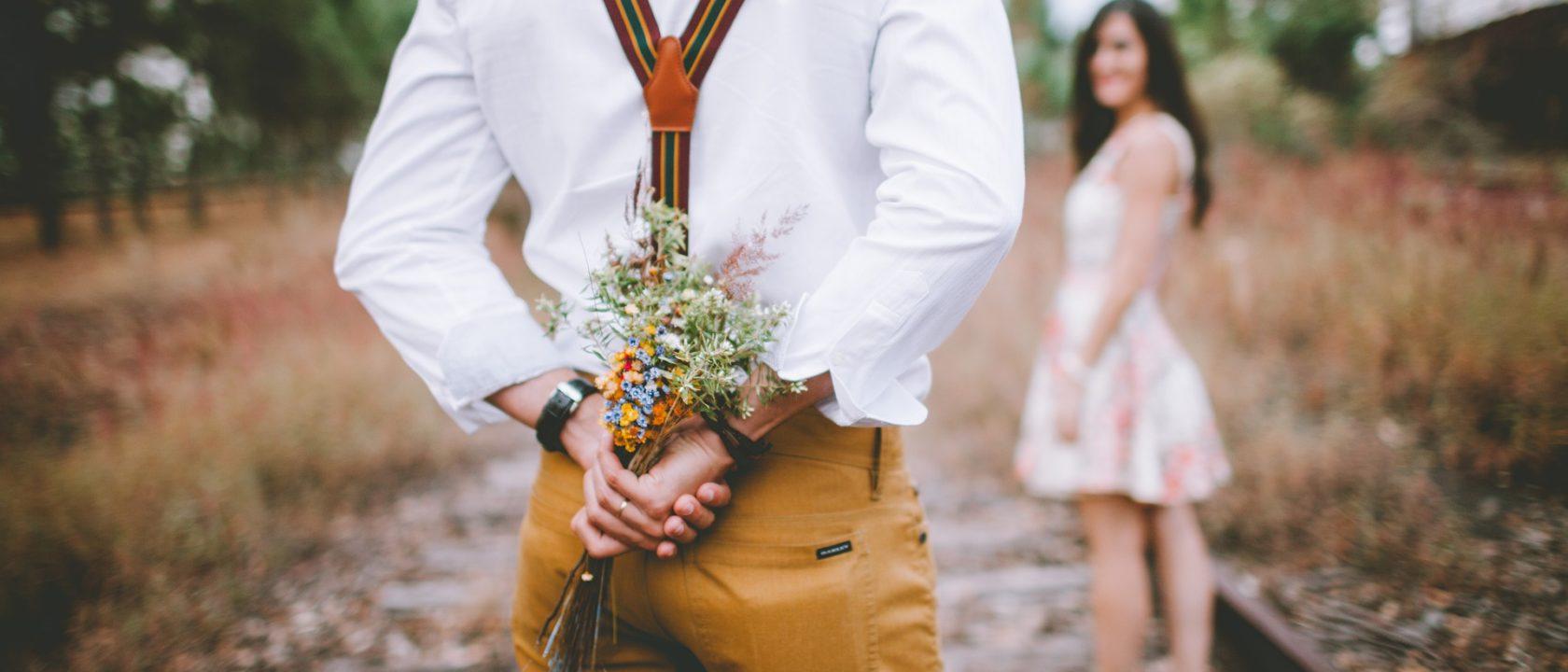 Adam, kadına sürpriz yapmak için arkasında bir demet çiçek gizliyor