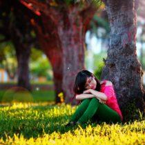 Özgüvensiz bir kız bir ağacın altında düşünüyor.