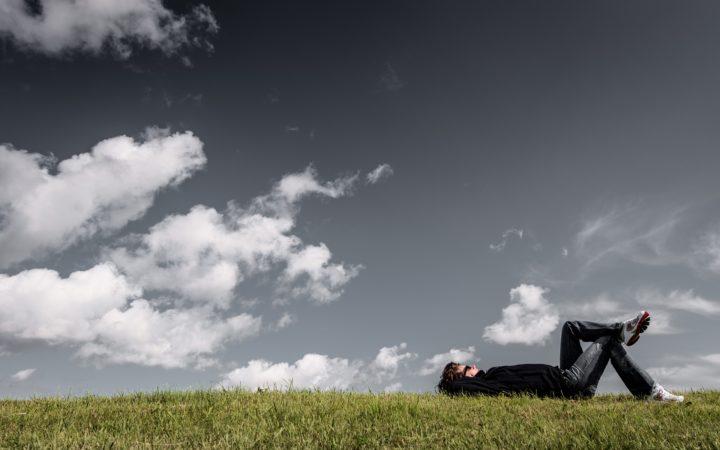 Bir adam çimlere uzanmış bulutları izliyor.