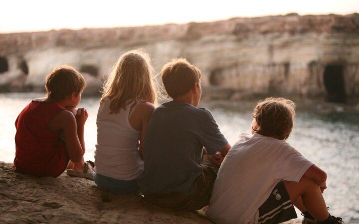 Biri kız dört çocuk toplanmış nehri izliyorlar.