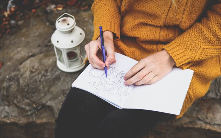 Bir kadın parkta oturmuş çizim defterine bir şeyler karalıyor.