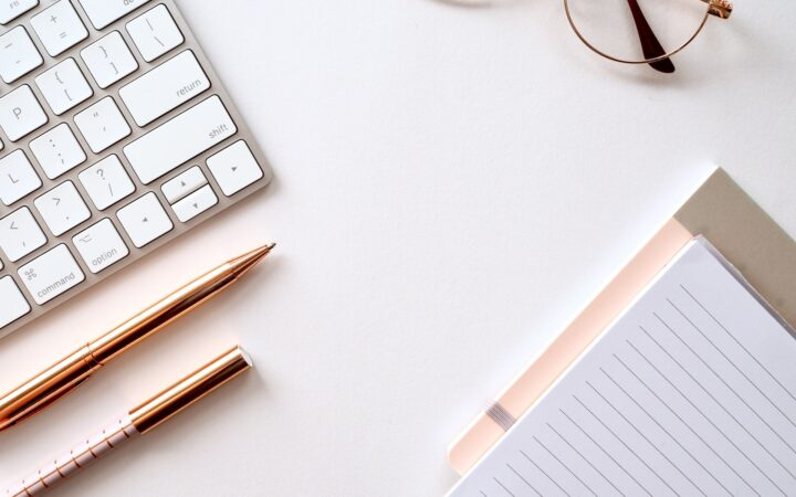 Masanın üzerinde duran iki adet kalem, klavye, not defteri ve gözlük.