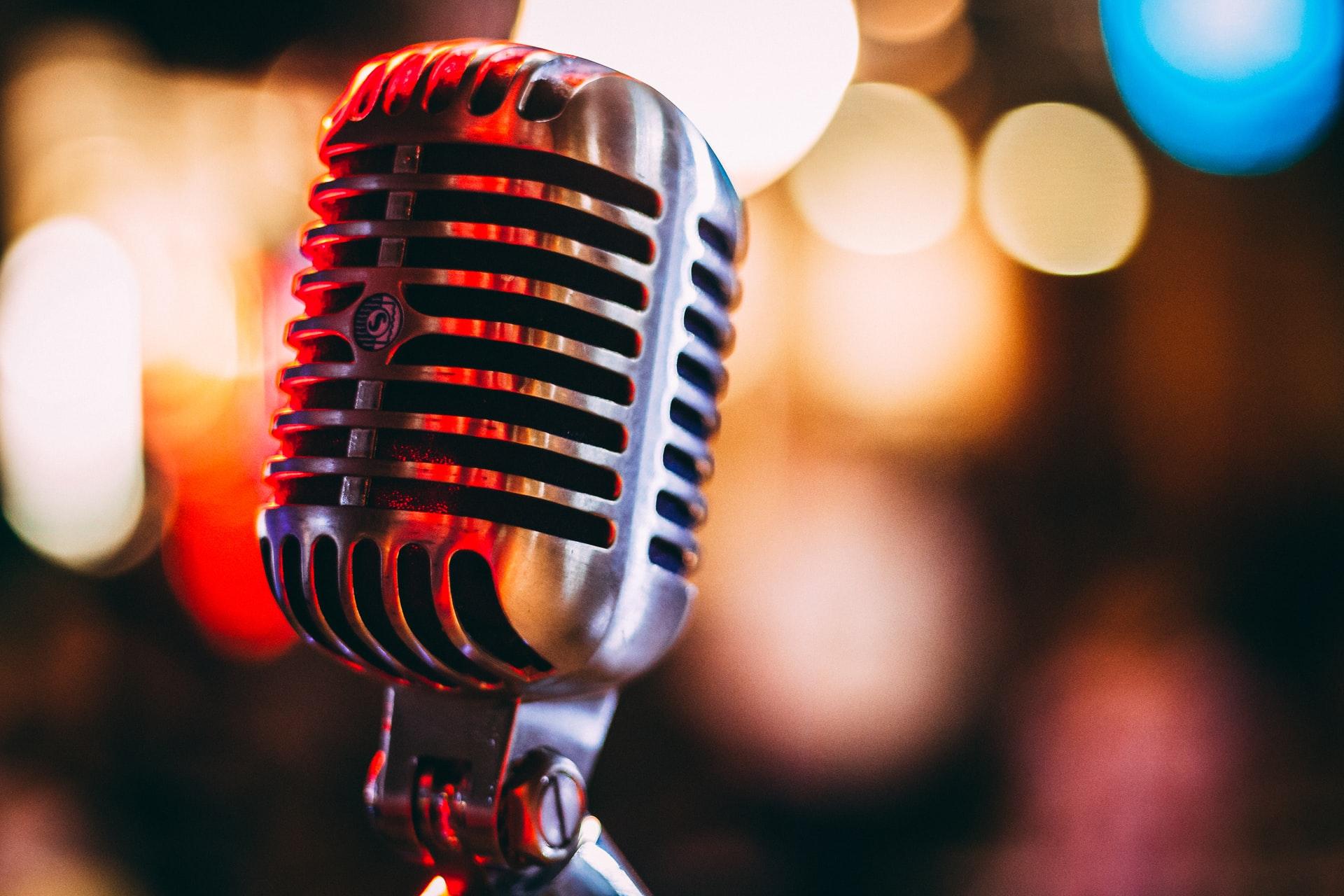 Rengarenk konser ışıklarının altında duran eski tarz bir radyo mikrofonu.