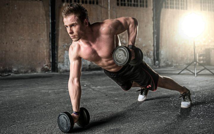 Bir fitnessçı ağırlıklarla vücut geliştirmeye çalışıyor.