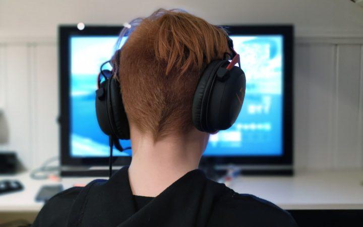 Bilgisayarın karşısında oyun oynayan kulaklıklı bir genç.