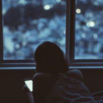 Yatarak telefonuna uygulama indiren kadın.