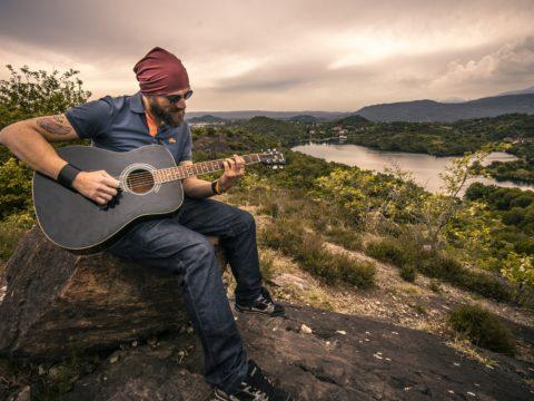 Doğada gitar çalan bir adam.