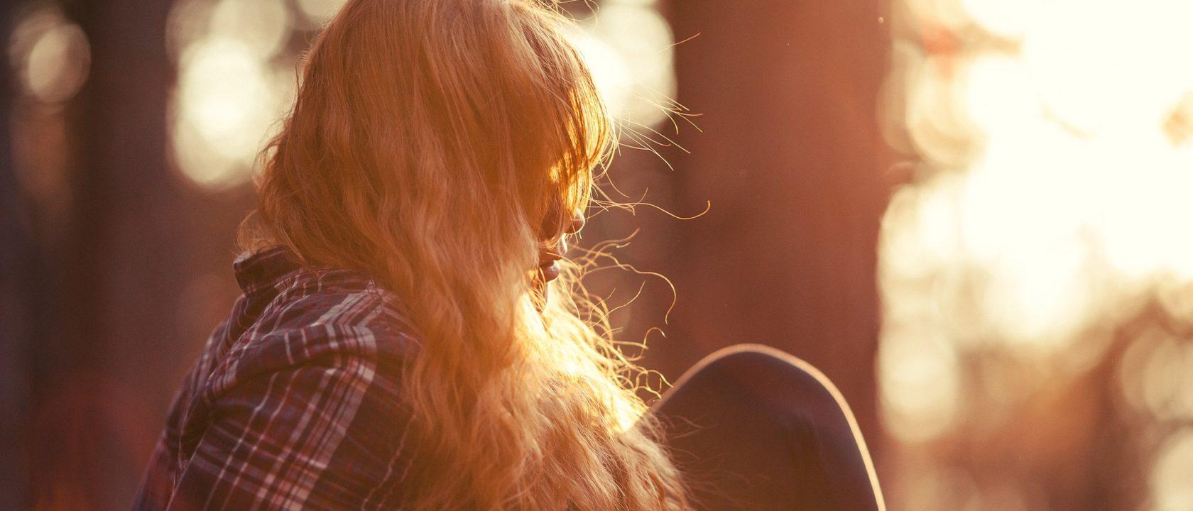 Sarışın bir kız gün batımını izliyor.