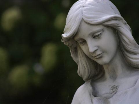 Mutsuz görünümlü bir heykel, yere doğru bakıyor.