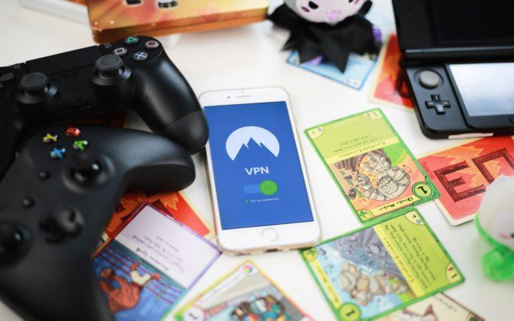 Beyaz bir masa üzerinde duran oyun kartları, telefon ve konsol kontrolcüleri.