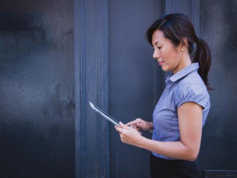 Resmi giyimli Asyalı bir kadın elindeki tableti inceliyor.