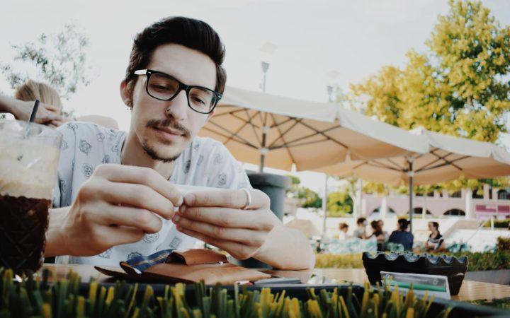 Kafede oturup kola içen kalın gözlüklü genç