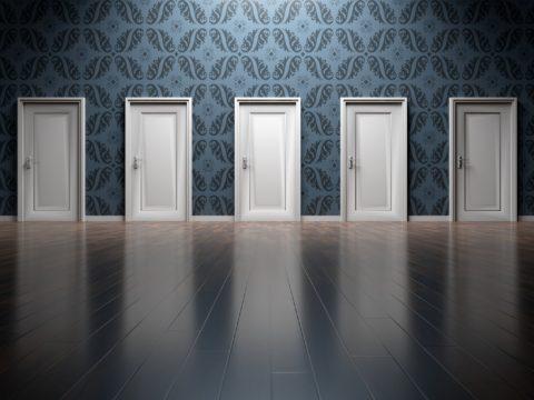 Boş bir holde yan yana dizilmiş kapılar.