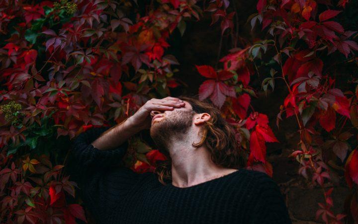 Kırmızı çiçekler arasında başını tutup acı çeken bir adam. Kırmızı hapın acı tadını simgeliyor.