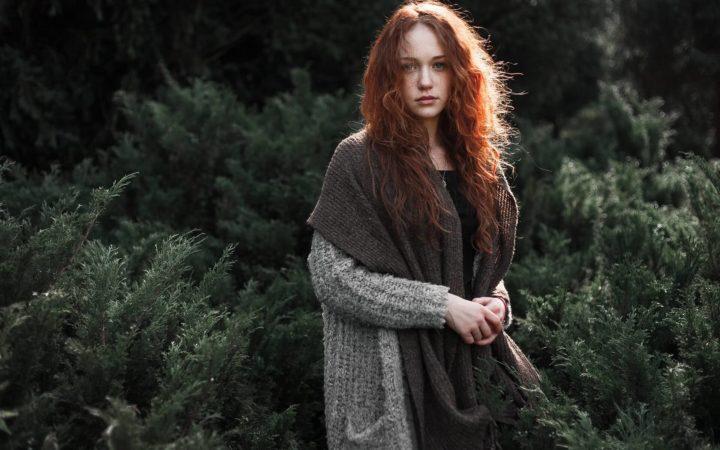 Kızıl saçlı bir kız ormanda geziyor.
