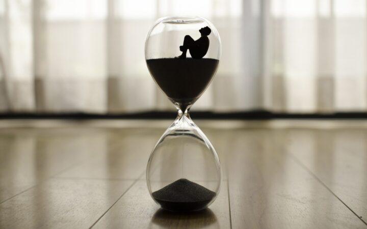 Bir adam kum saatinin içinde acı çekerek bekliyor.