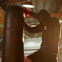 Bir kickbox'çu kum torbasını tepesinden yakalamış tekmeliyor.