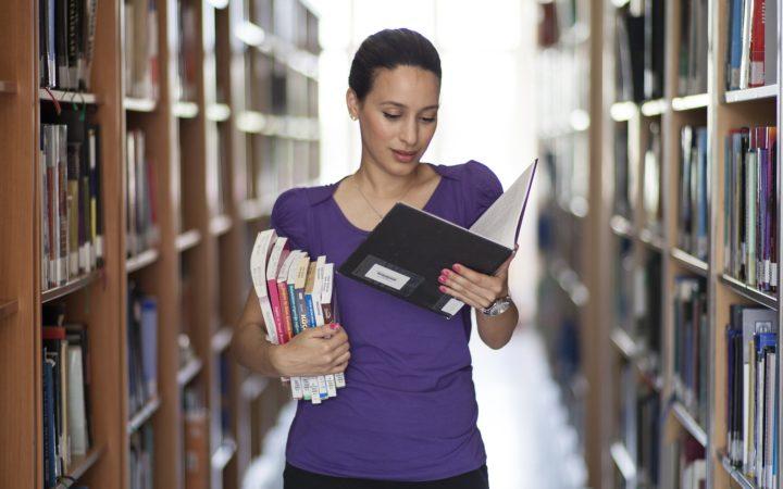Kadın elinde bir tomar kitapla yürüyor.