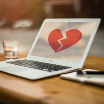 Bir laptop ekranında kırılmış bir kalp resmi var.