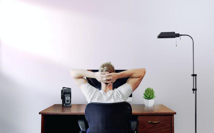 Bir adam çalışma masasında oturmuş, ellerini başının arkasında birleştirmiş, düşünüyor.