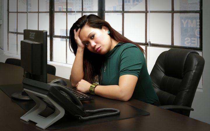 Ofiste son derece bunalmış bir kadın, başını eline koymuş mutsuz bir şekilde etrafa bakıyor.