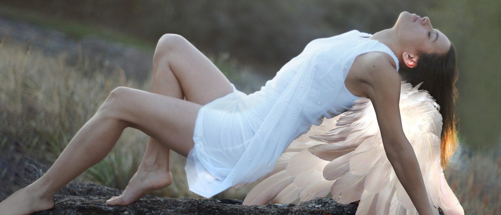 Bir melek kayanın üzerine yayılıp oturuyor.