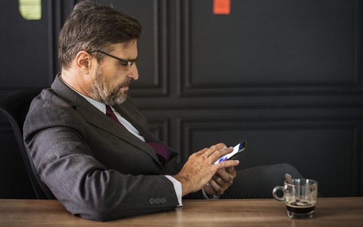 Telefonundaki haberlere bakan iş adamı.