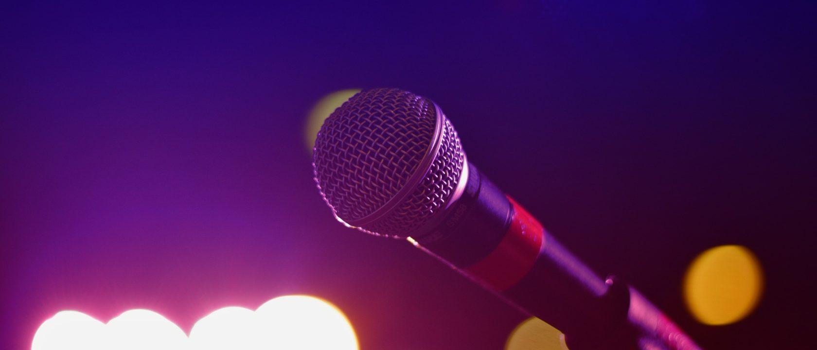 Sahne ışıkları altında bir mikrofon.