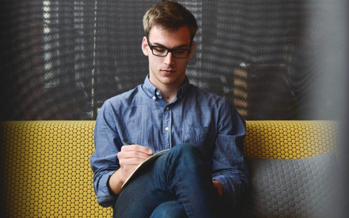 Gözlüklü genç bir adam not tutuyor.