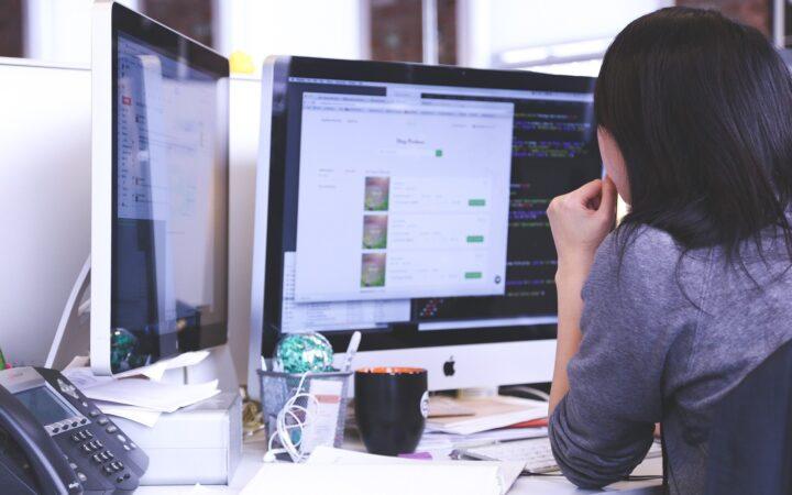Ofiste iki tane büyük profesyonel monitörün karşında çalışan bir ofis elemanı.