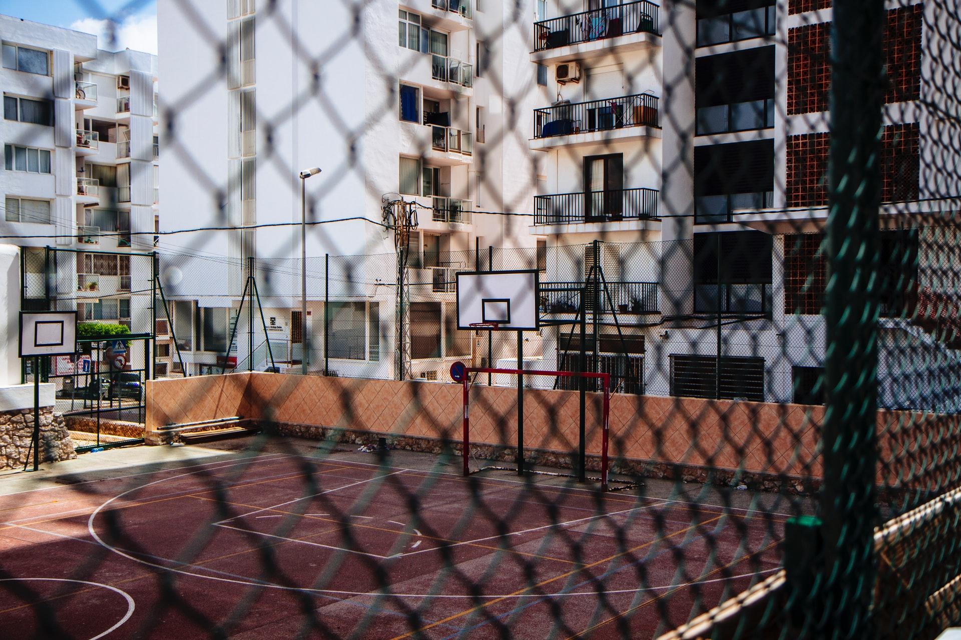 Boş bir basketbol-futbol sahası tel örgülerin ardından görünüyor.