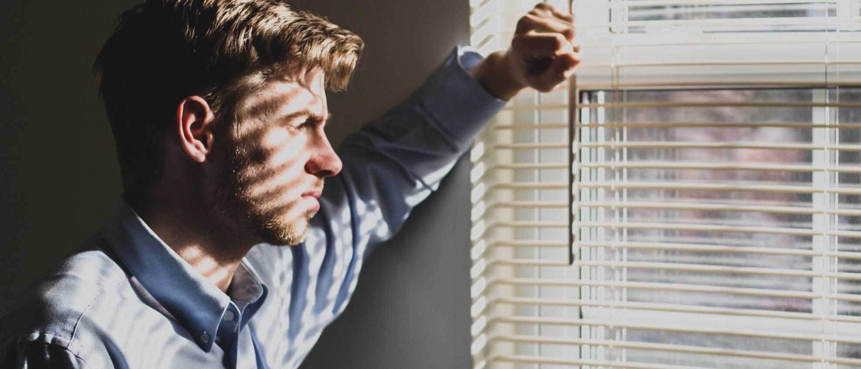 Depresyondan kurtulma yolu arayan düşünceli adam, pencereden dışarıya bakıyor.