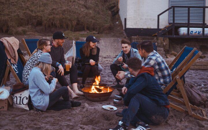 Plajda toplanıp ateş yakmış gençler sohbet ederken.