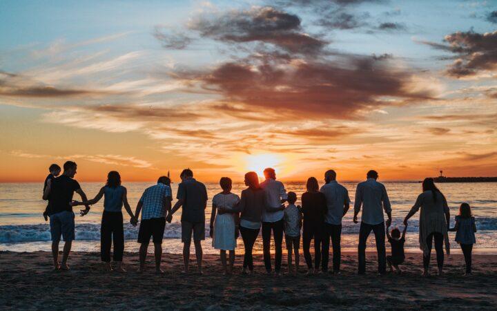 Birkaç aile sahilde durmuş gün batımını izliyorlar.