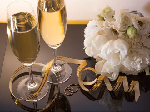 Cam bir yüzey üzerine son derece şık şarap kadehleri ve nikah yüzükleri duruyor.