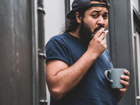Sigarayla kahve içen şapkalı şişman genç