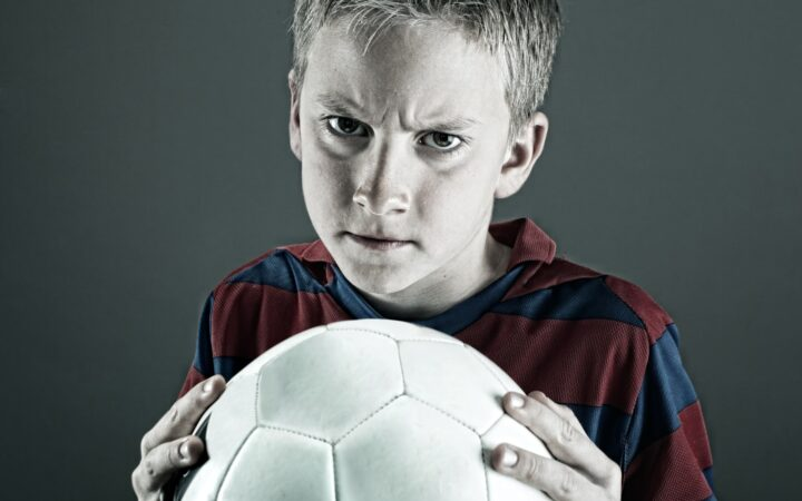 Futbol topunu sıkı sıkı tutan çocuk sinirli bakışlar atıyor.