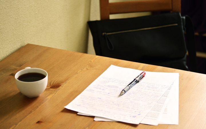 Masasının üzerinde bir kahve ve çözülmeyi bekleyen sorunlar listesi var.