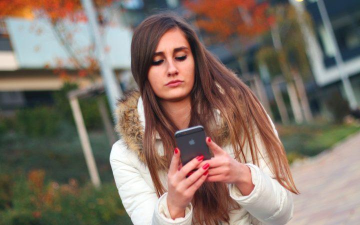 Yüzünü ekşiterek telefonuna bakan genç kız.