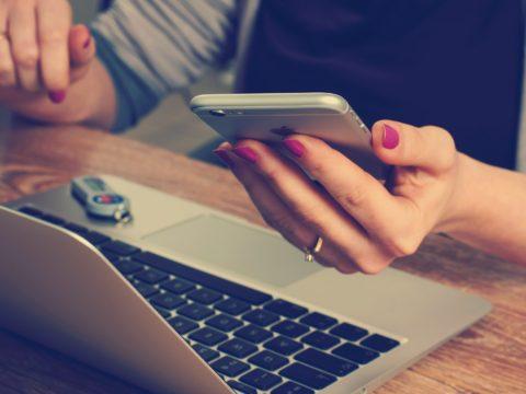 Bilgisayarının önünde telefonuna bakan kadın.