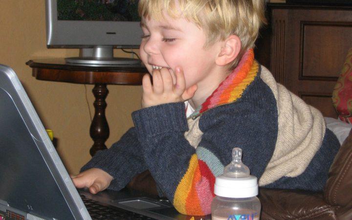 Bilgisayar başındaki çocuk pis pis gülümsüyor. Çilekli süt dolu biberonunu da yanına almış.