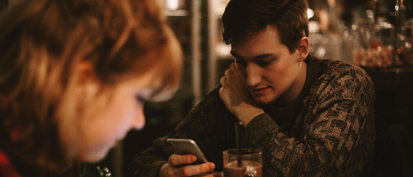 Genç bir adam barda oturmuş telefonuna bakıyor.